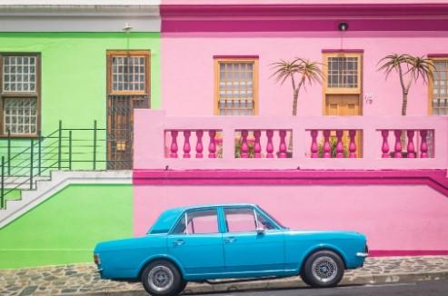 Blauwe oldtimer voor mooi gekleurde huizen